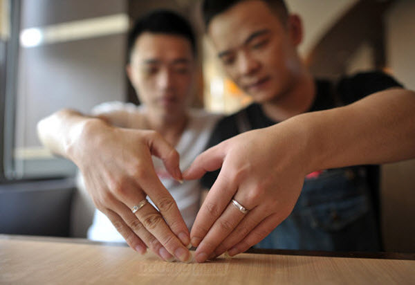 Two Chinese gay men forming a heart with their hands with rings on their fingers.