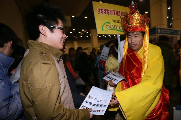 A recruitment fair worker dressed as Xuanzang distributing materials to job applicants.
