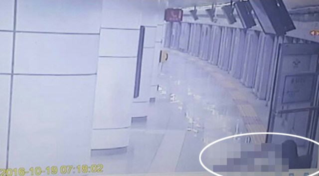 The victim, circled, collapses after coming through an emergency door on the platform. He died in hospital. / Yonhap