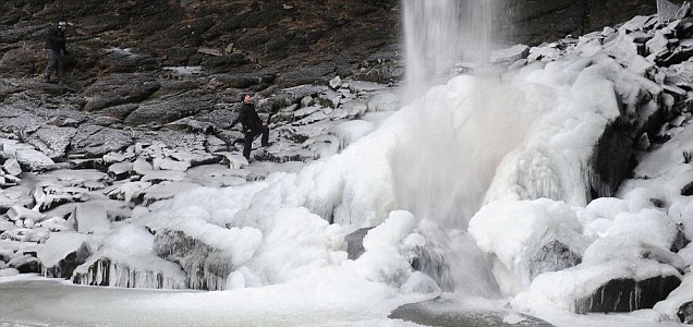 A hiker looks at the spectacular frozen water fall at Hardraw