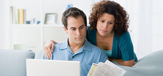 Couple looking at home finances on computer.