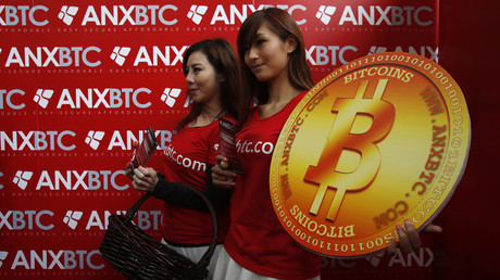 Attendants pose with a bitcoin sign during the opening of Hong Kong's first bitcoin retail store February 28, 2014 © Bobby Yip