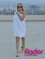 Lindsay Lohan show off her big breasts in reveling swimsuit at a pool in Hollywood -