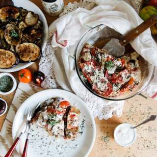 A lightened up version of a classic, this cold moussaka is layered with eggplant, potatoes and tomatoes, and served with tangy kalamata feta sauce.