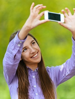 Teenage girl pictures of himself with smartphone