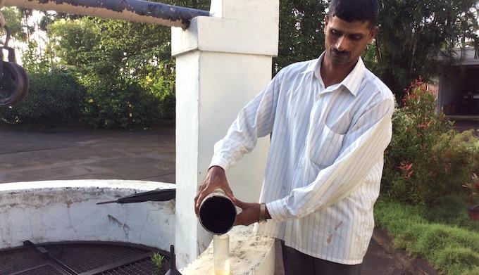 A farm worker measures rainfall in K. K. Naren's coffee farm. (Photo by S. Gopikrishna Warrier)