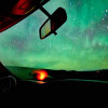 A steering wheel faces a sky full of the northern lights.