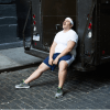 An overweight exerciser rests on the back of a UPS truck.