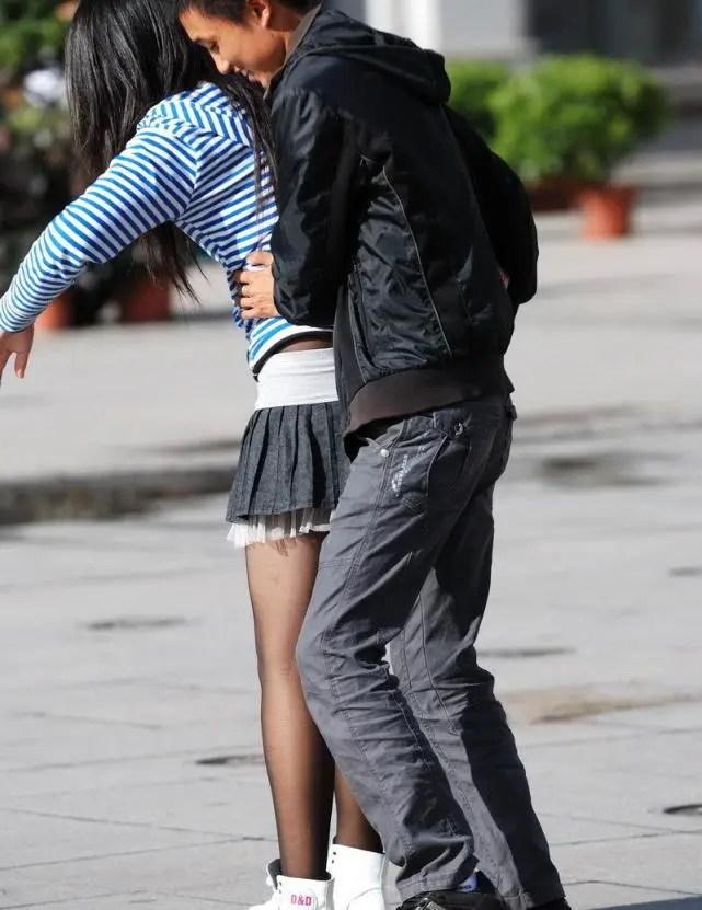 街拍時尚:美眉穿著超短裙在廣場上向男友投懷送抱秀恩愛,辣眼睛