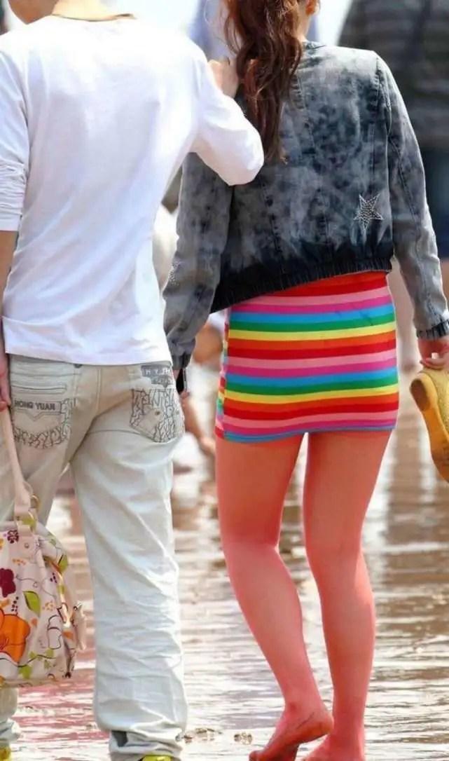 路人街拍,緊身包臀裙搭配紅色絲襪陪男友戲水的美女,腿真美