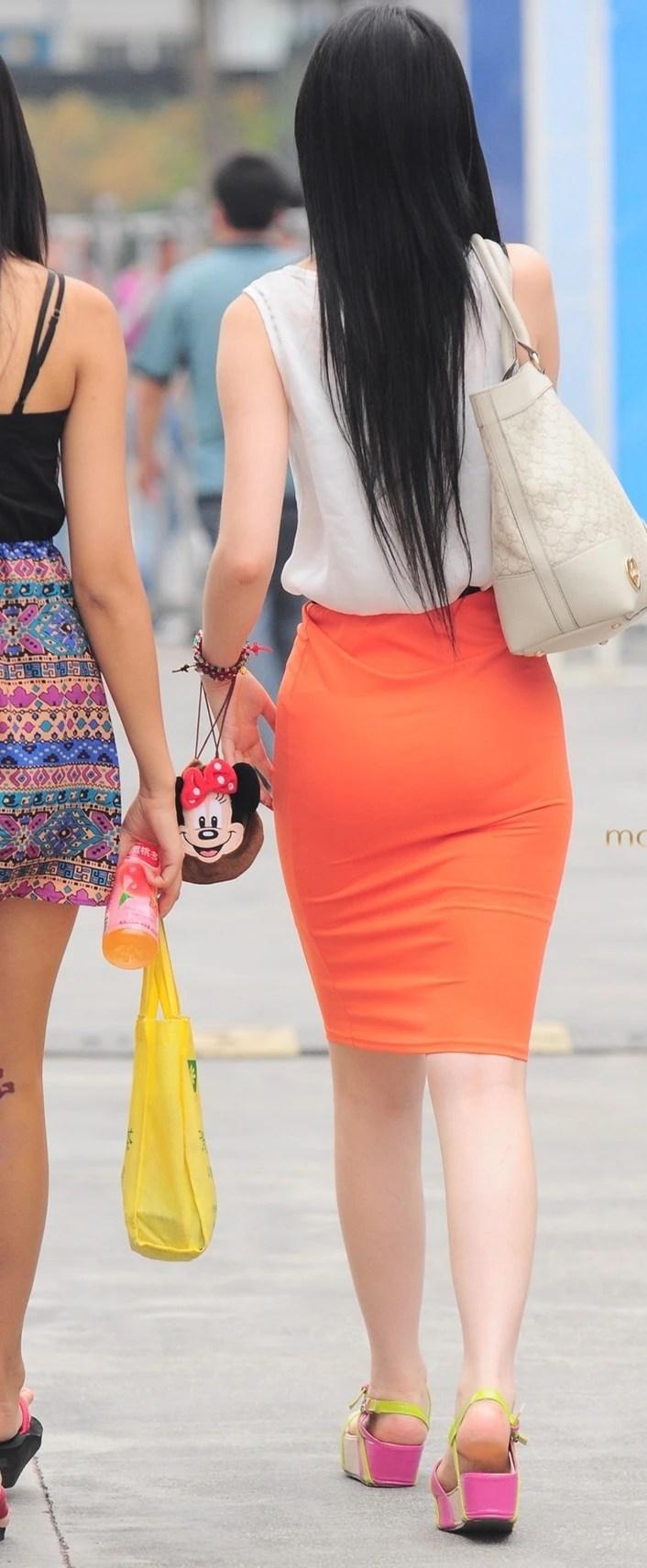 路人街拍,長發披肩S型身材的時尚少女,橘色包臀盡顯渾圓背影!