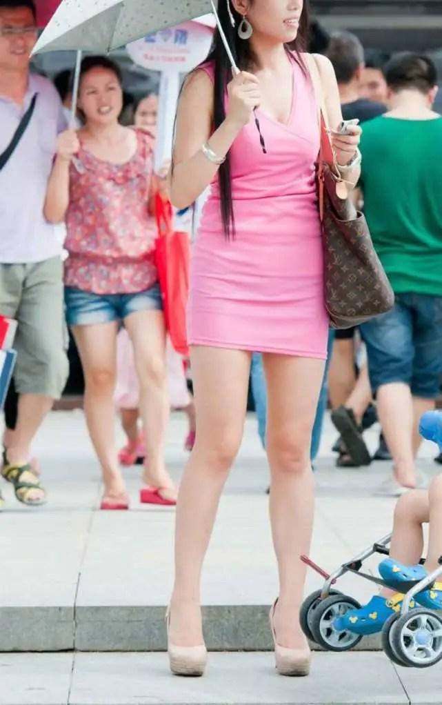 路人街拍,穿粉色包臀裙帶孩子逛街的時尚辣媽,腰細腿白美麗養眼