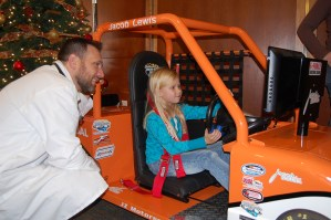 """Dr. LeRoy Eberly, a hospitalist at Akron Children's Hospital Mahoning Valley, checks out the """"bells and whistles"""" of the Dream Racer with patient Trinity Tubbs."""