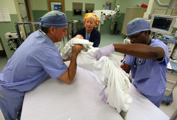 After surgery, Dr. Milo and OR staff move Jordan from the OR table to a crib