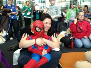 A Young Spider-Man sits with his mom and others in the atrium lobby to watch his hero wash windows.