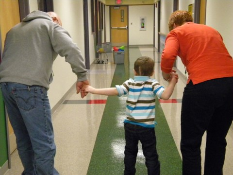 Luke gets assistance in rehab from his dad, Chad, and physical therapist Kate.