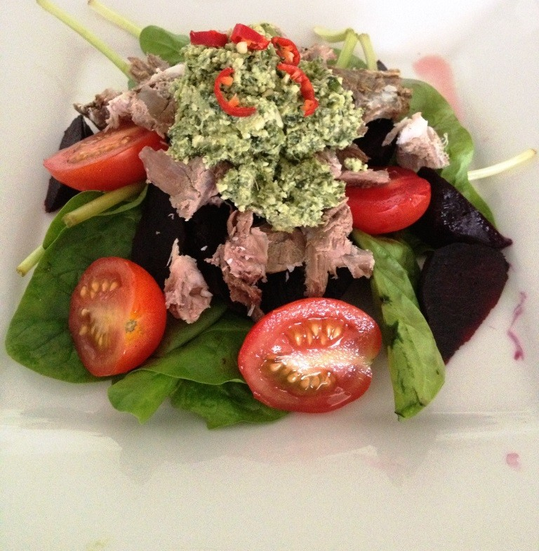Lamb with baby spinach, cherry tomatoes, and basil pesto