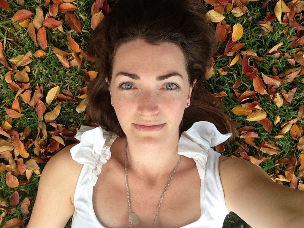 Blue-eyed girl daydreaming... lying on the grass under a tree, surrounded by autumn leaves