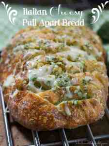 Italian Cheesy Pull Apart Bread |Crazy good and addictive this Italian Cheesy Pull Apart Bread is sure to be a crowd pleaser. The loaf is filled with a buttery garlic, pesto and Italian herb mixture then generously stuffed with mozzarella cheese to create each perfect bite for this pull apart Italian bread.
