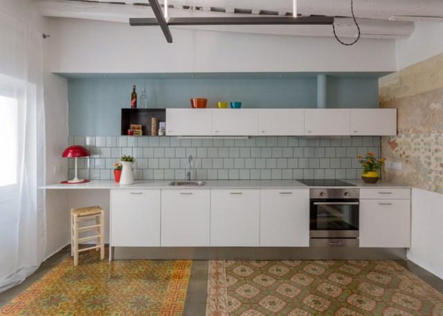 Continuando con la misma gama de color, la cocina se alicata de azulejo gris azulado. Los muebles son blancos; se repite la colocación de una caja a modo de estante.