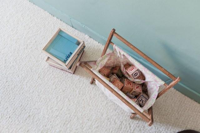 Pared en azul turquesa y preciosa alfombra en crudo. El rodapie está pintado en el mismo color que la pared.