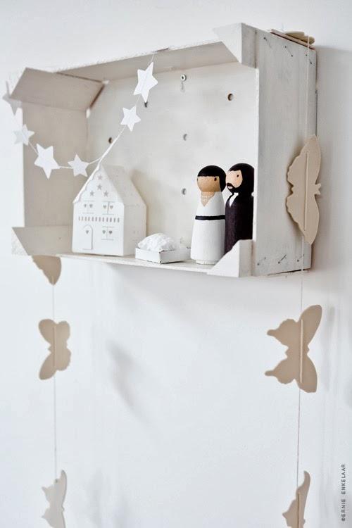 Belén de figuritas de madera colocado en un a caja de fruta. las guirnaldas son de cartón y hechas a mano.