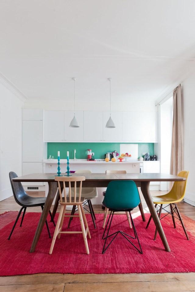 Comedor compuesto por mesa y sillas diferentes y de distintos colores.
