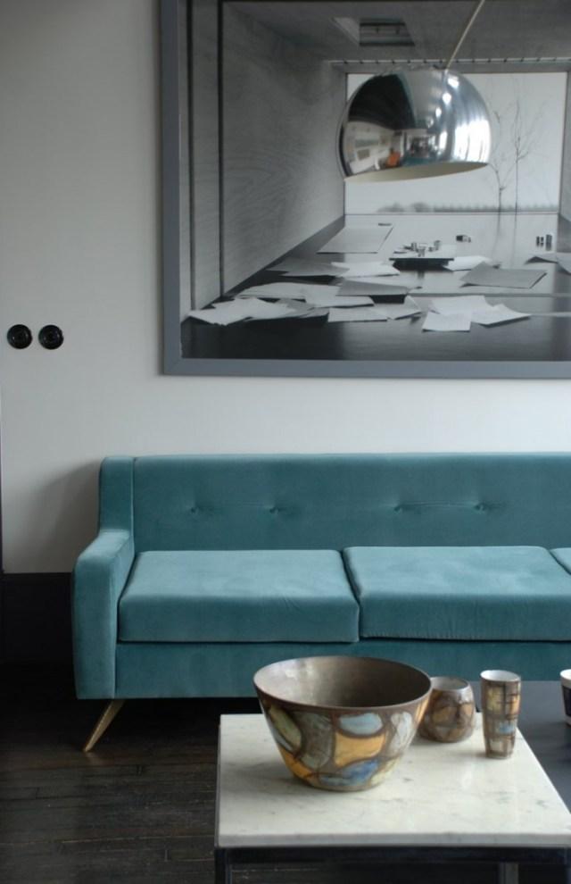 Precioso sofá verde agua sobre un lienzo gris.