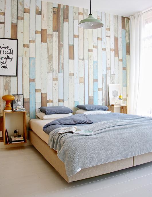 En el dormitorio principal se ha empapelado la pared más importante, la que contiene al cabecero, con un papel especial de tablones de madera gastada. Se incluye una lámpara industrial en verde menta preciosa.