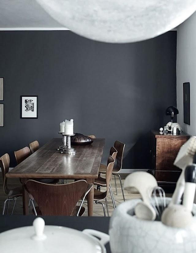 Una pared pintada en gris pizarra hace de telón de fondo para los elementos cercanos, como mesa, sillas, lámpara, etc...