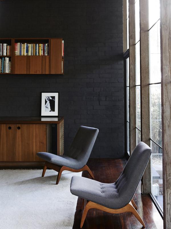 Los paramentos oscuros con mobiliario hecho a medida y alfombra clara es una constante que se repite.