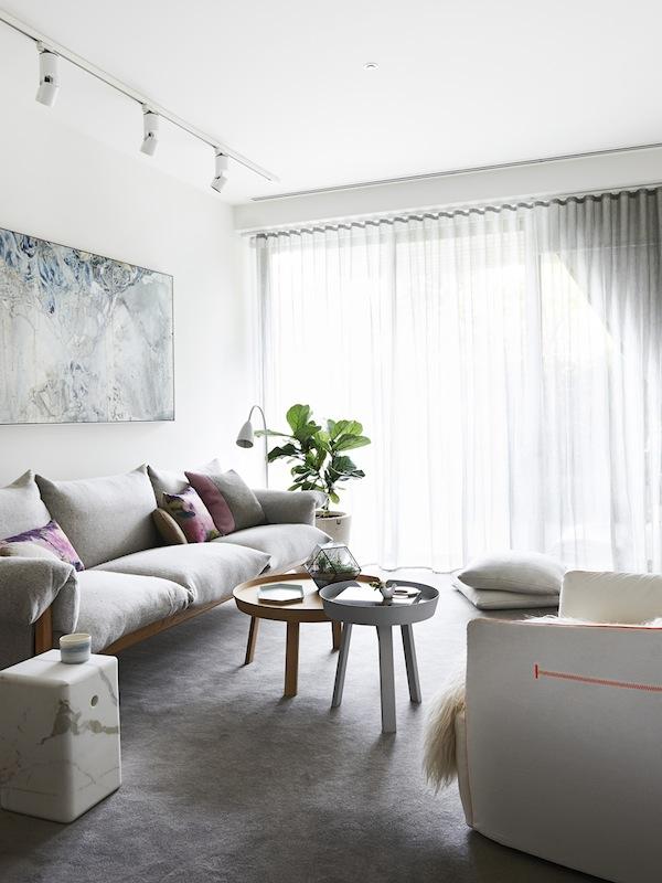 La zona de estar con el sofá de estructura de madera y demás elementos blancos dan protagonismo al cuadro que se encuentra encima del sofá.