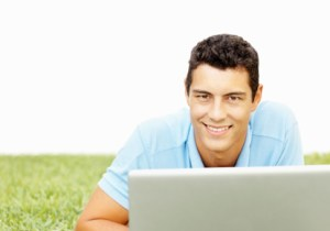 Smiling casual young man using a laptop computer outdoors