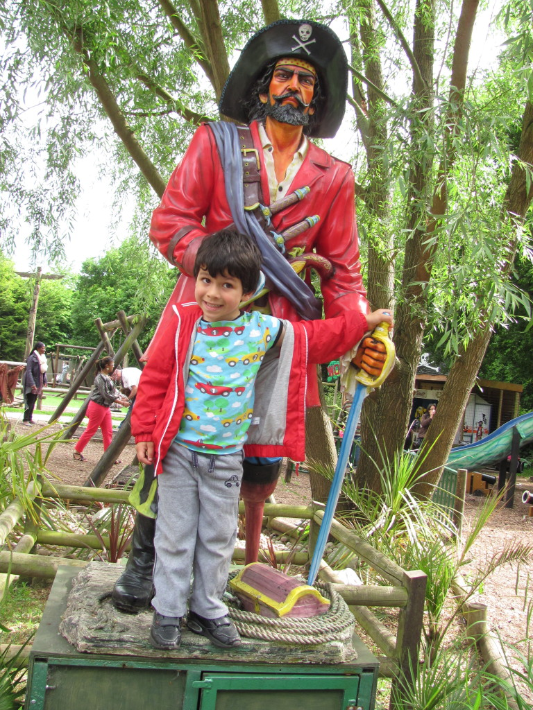 boy posing with a pirate figure