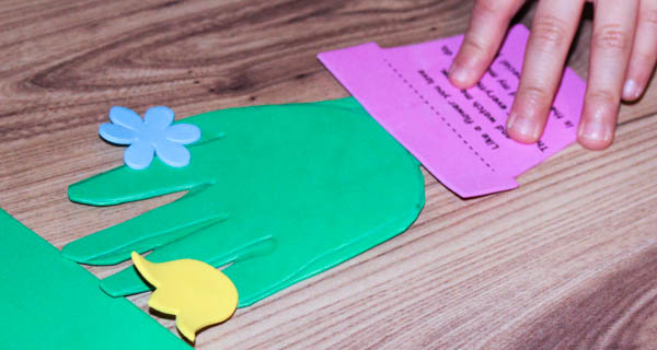 decorating handprint with flowers for a flowerpot craft