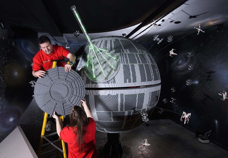 SHOT 13. Caption. ONE OF THE WORLD'S BIGGEST EVER LEGO® STAR WARS™ MODELS INSTALLED AT THE LEGOLAND® WINDSOR RESORT.   LAST PIECES PUT IN PLACE ON 500,000 LEGO® BRICK DEATH STAR LEGOLAND® Model Makers Giorgio Pastero and Phoebe Rumbol lift the top piece into place, onto one of the biggest and most impressive LEGO® Star Wars™ models ever created - a 500,000 brick LEGO® Star Wars™ recreation of The Death Star. The operation took three days as the massive new 2.4 metre wide, 3 metre high creation was carefully hoisted into position and the final bricks were put in place. The hefty 860kg perfectly spherical model took 15 Model Makers three months to build and will be the centrepiece of an epic new finale at the LEGO®Star Wars™ Miniland Model Display when the Resort opens on 11 March and guests will be able to trigger special effects and bright the scene to life. TM & © Lucasfilm Ltd. All rights reserved