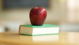 An apple and a book sitting on a desk in a classroom
