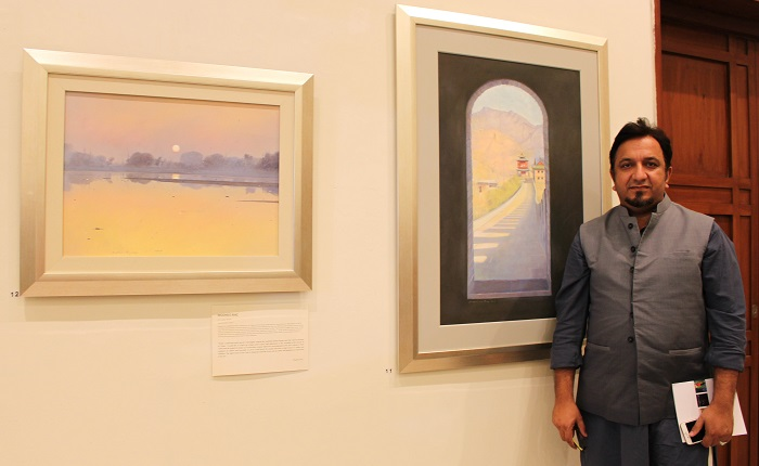 Mughees Riaz, Lahore-based artist, with his artworks paintings at joint exhibition by Pakistani and Chinese artists at PNCA in Islamabad on 18 Oct. 2016. Photo: Sana Jamal