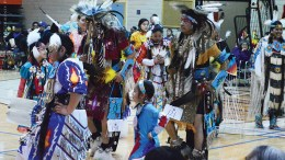 Group of Native American adults and children in dance regalia dancing at the 46th ISU powwow.