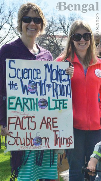 Women holding a poster with 'Science Makes the World go Round', 'EARTH = LIFE' and 'FACTS ARE Stubborn Things' (attributed to John Adams, 1770).