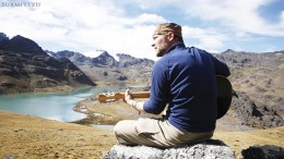 Survivorman Les Stroud playing guitar in scenic area with mountains and river in the background.