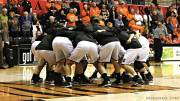 Women's basketball players huddled on the court.
