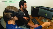 Woman using VR headset while a man views image on computer monitor