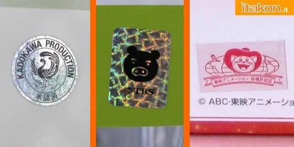 Da sinistra a destra: sticker Kadokawa Shoten, presente su tutti i prodotti del mercato Giapponese, e in modo incostante su quelli esportati; sticker TBS, presente solitamente su tutti i prodotti, inclusi gli esportati; sticker TOEI Animation, esiste in diverse colorazioni in base alla zona di distribuzione (Oro, Argento ecc...), talvolta non presente sugli esemplari esportati in Europa o America