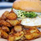 Fried Egg Sandwich made with Two Eggs Fried, Cheddar Cheese, Aioli and Fresh Avocado with a side of Crispy Potatoes
