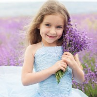 happy little girl is in a lavender field holding bouquet of flowers