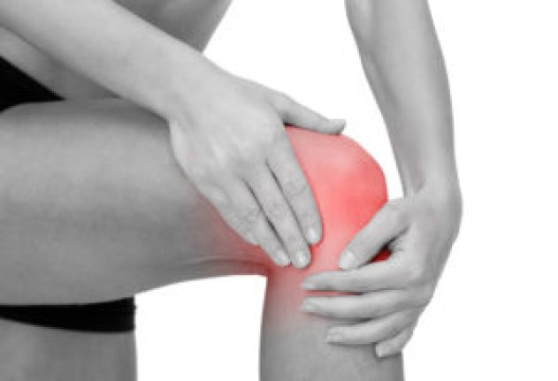 Knee Pain, fitness, healthcare and medicine concept - close up of female hands holding knee