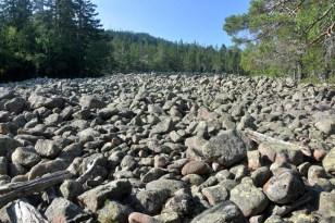 Wypiętrzony kamienisty brzeg morza gdzieś w połowie wysokości wzgórza.