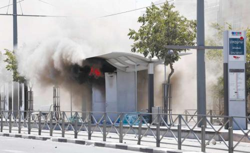 "A light-rail stop on fire, July 2014. Rioters of the ""Jerusalem Intifada"" chose to attack and damage a symbol of coexistence that serves both populations – the light rail. (Sliman Khader, Flash 90)"