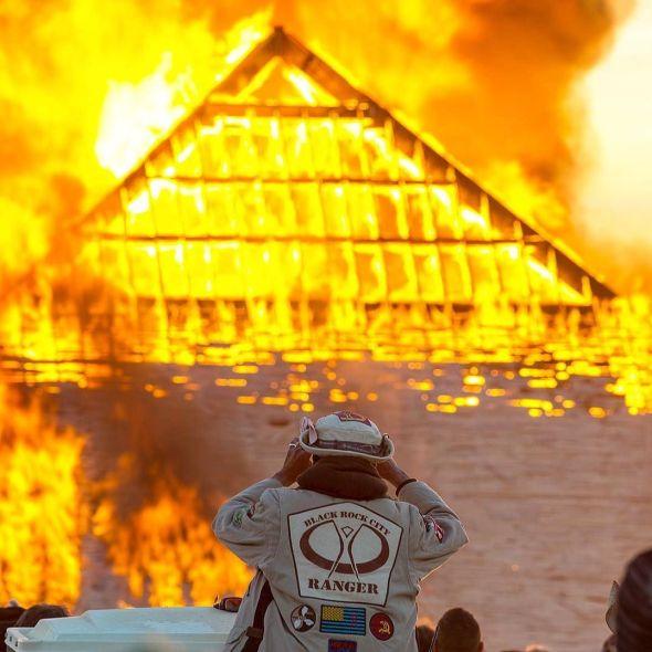 Catacomb of Veils pyramid set ablaze while a BRC ranger looks on.